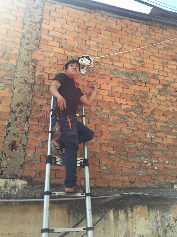 nhân viên kĩ thuật thi công lắp đặt camera an ninh cho công trình đang thi công